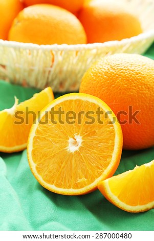 Ripe oranges in basket on green background - stock photo