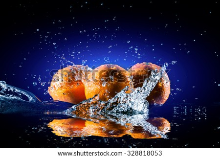 ripe oranges lying on the mirror in a spray of water on dark backgroun