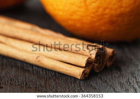 ripe oranges with cinnamon on wooden table