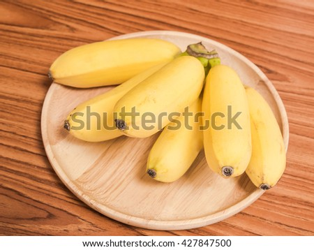Ripe organic banana on wooden plate,closeup shot. - stock photo