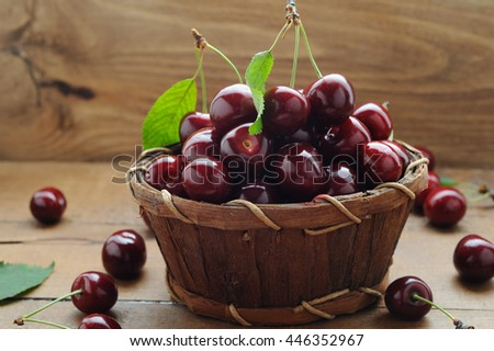 Ripe organic cherries in a basket on wooden background