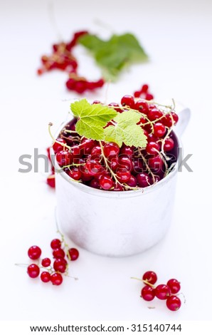 Ripe organic red currant in the mug - stock photo
