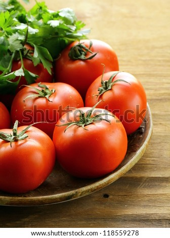 ripe organic tomatoes on a wooden table - stock photo