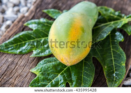Ripe papaya with green leaf on wooden background.