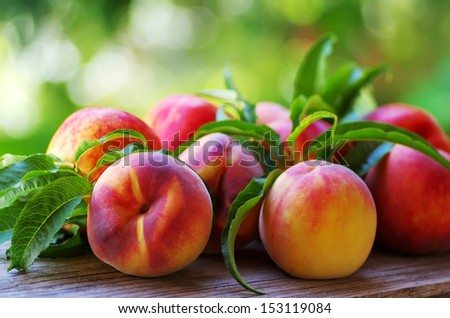Ripe peaches and leaves on table - stock photo