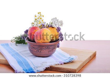 Ripe peaches in a plate on a table on a white background. - stock photo