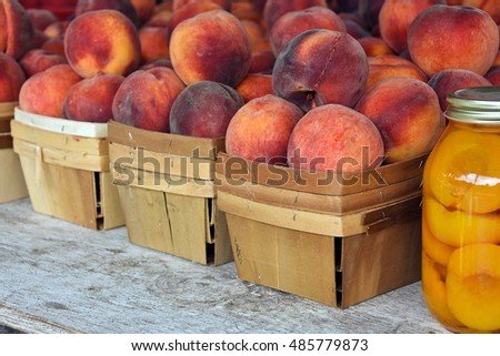 ripe peaches in produce boxes with canned peaches in mason jar at the farmer's market