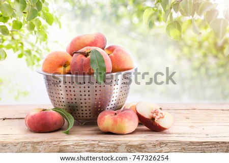 Ripe peaches with leaves on a wooden board on a background of green leaves