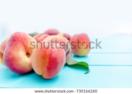 Ripe peaches with leaves on rustic wooden table. Shallow depth of field.