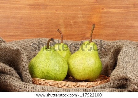 Ripe pears in sack on wooden background close-up