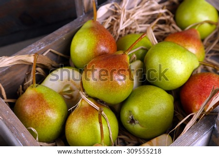 Ripe pears in wooden box close up