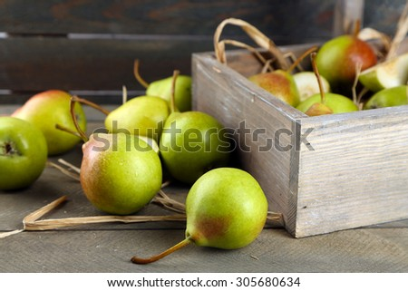 Ripe pears in wooden box on table close up - stock photo