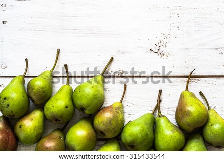 Ripe pears on wood. Fresh summer fruits on white rustic wood background with copy space, top view, close-up. - stock photo