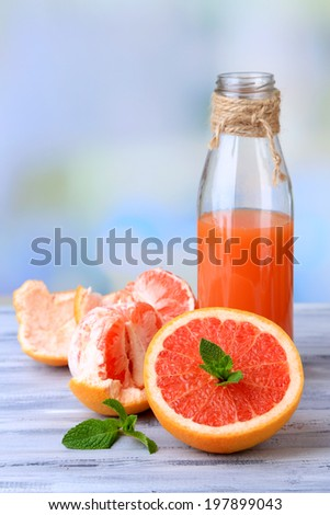 Ripe peeled grapefruits and fresh juice on color wooden table, on bright background
