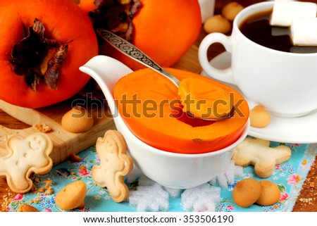 Ripe persimmon for breakfast with biscuits and coffee, selective focus - stock photo