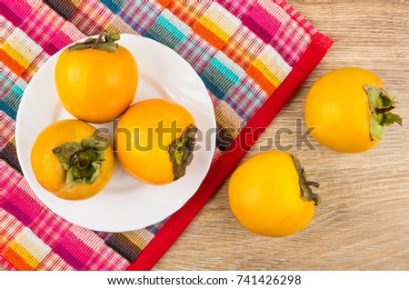 Ripe persimmons in white plate on checkered napkin and on wooden table. Top view