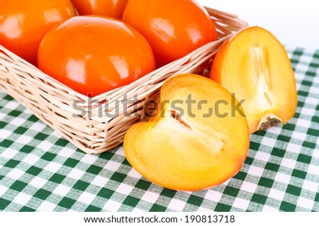 Ripe persimmons in wicker basket on table close-up - stock photo