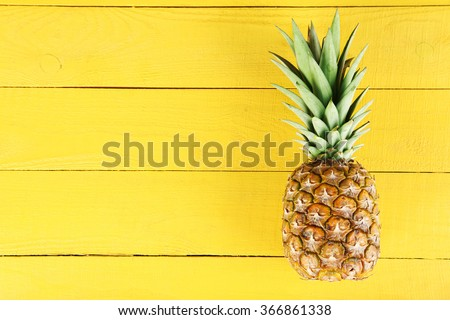 Ripe pineapple on a yellow wooden background - stock photo