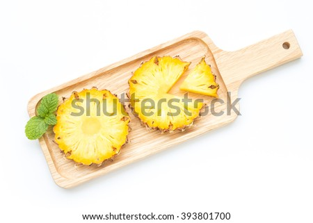 Ripe pineapple slices on wood plate on white background - stock photo