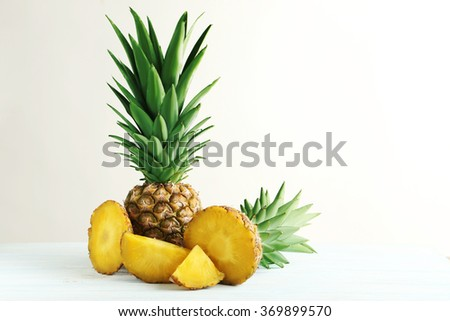 Ripe pineapples on a white wooden background - stock photo