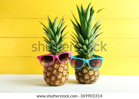 Ripe pineapples with sunglasses on a white wooden table - stock photo