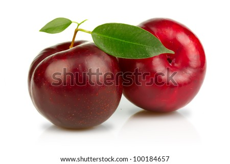 Ripe plums fruits with green leaves isolated on white background