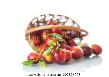 ripe plums in a basket on a white background - stock photo