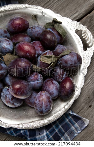 Ripe plums in an old aluminum plate