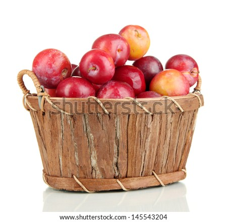 Ripe plums in basket isolated on white