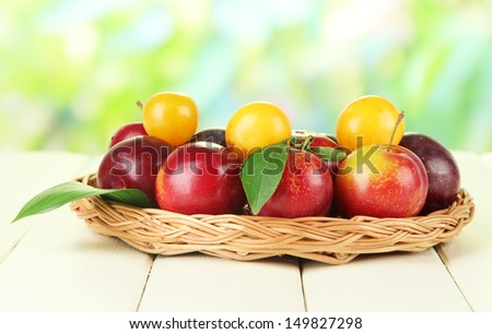 Ripe plums in basket on wooden table on natural background - stock photo