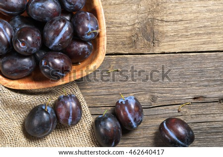 Ripe plums in bowl on rustic wooden table, top view