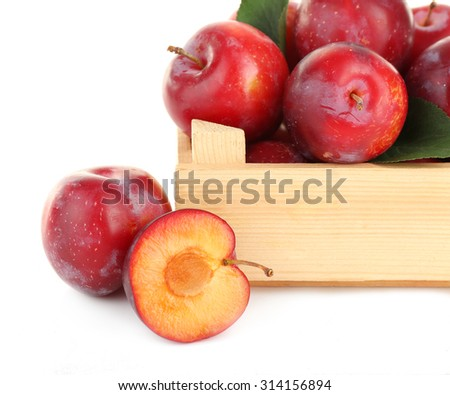 Ripe plums in wooden crate isolated on white