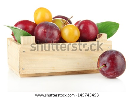 Ripe plums on wooden box isolated on white