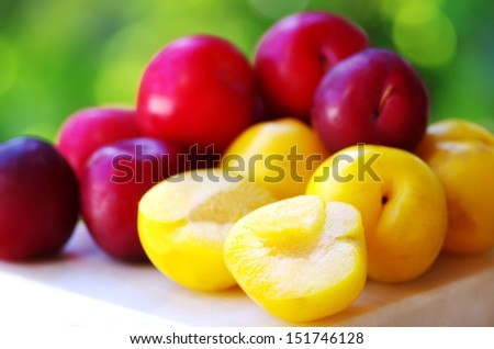 Ripe plums on wooden table and sliced plum