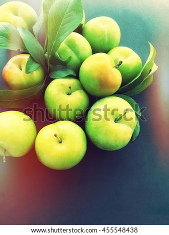 Ripe plums with leaves, glow and copy space  - stock photo