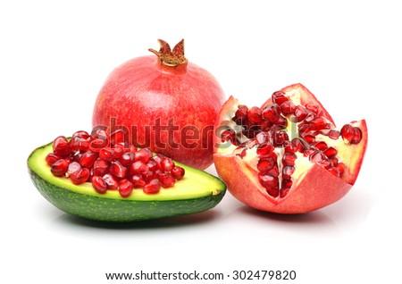 Ripe pomegranate, avocado, pomegranate seeds on white background - stock photo