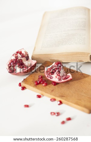 Ripe pomegranate fruit  with cutting board and book - stock photo