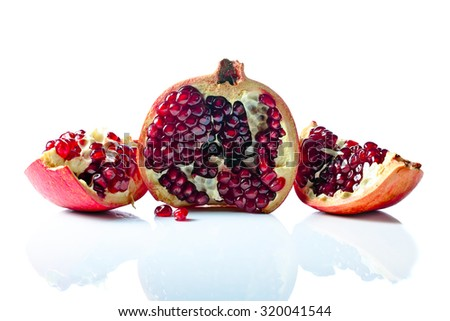 ripe pomegranate isolated on a white reflexive background - stock photo