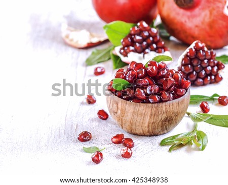 Ripe pomegranate seeds in a wooden bowl on  white  vintage background. - stock photo