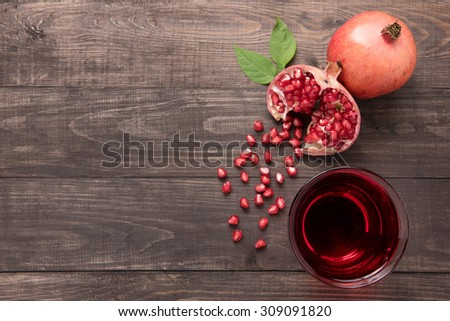 Ripe pomegranates with juice on wooden background. - stock photo