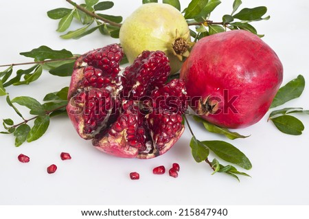 ripe pomegranates with leaves - stock photo