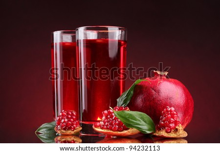 ripe pomergranate and glasses of juice on red background