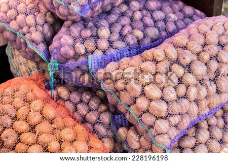 Ripe potatoes in sack for background - stock photo