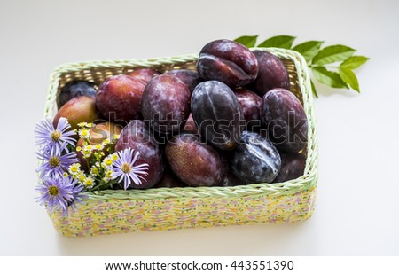 Ripe Prunes (plums)  In Decoupage Basket decorate with flowers and leaves - stock photo
