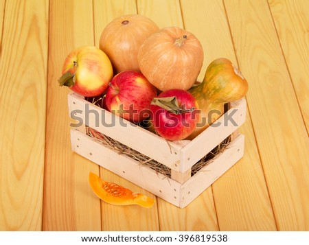 Ripe pumpkins and apples in a wooden box on a background of light wood. - stock photo