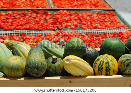 Ripe pumpkins, gourds and dried tomatoes on the counter - stock photo