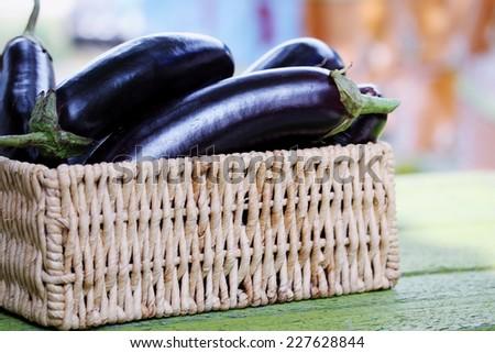 Ripe purple eggplant in a wicker basket - stock photo