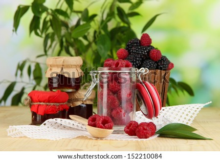 Ripe raspberries and blackberries on wooden table on natural background