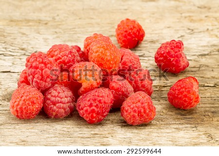 ripe raspberries closeup on wooden background - stock photo