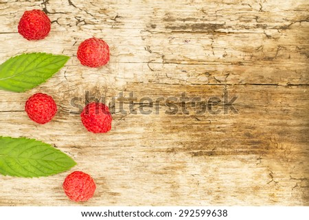 ripe raspberries with mint leaves on wooden background - stock photo